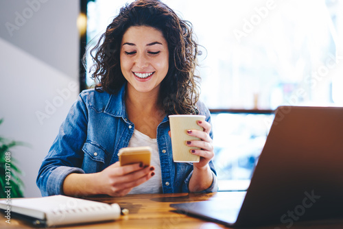 Obraz Happy hipster girl with coffee to go using cellular device for online messaging and chatting in social media, cheerful female blogger with takeaway cup connecting to 4g for browsing website - fototapety do salonu
