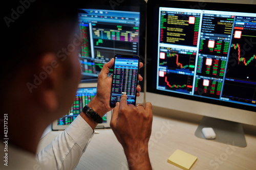 Obraz Close-up image of trader trading stocks and options in stock market. and monitoring proces via application on smartphone - fototapety do salonu