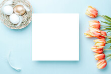Easter Holiday. Golden, White Colour Egg In Basket With Spring Tulips, Feathers On Pastel Blue Background In Happy Easter Decoration. Spring Holiday Top View With Copy Space.