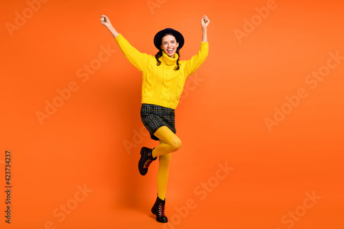 Full size photo of optimistic girl hands fists dance wear yellow sweater cap skirt shoes isolated on orange background
