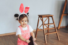 Asian Girl Of Two Years Old Is Dressed In Red Dress With White Polka Dots. The Child Is Swinging On Horse Swing. Child Has Rabbit Ears On Head. There Is Small Stepladder Against Backgorund Gray Wall