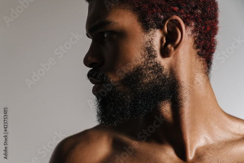 Foto Black shirtless bearded man posing and looking aside