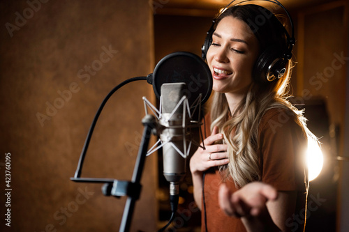Obraz na plátně Woman singing and recording songs in music studio