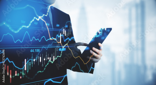 Trading and investment concept trader silhouette with digital tablet and virtual screen with financial chart graphs and candlestick Fototapet