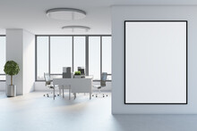 Blank White Poster In Black Picture Frame On Light Wall In Stylish Open Space Office With Modern Furniture, Tree In Metallic Flowerpot On Concrete Floor And City View From Big Window