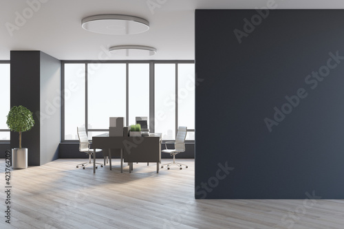Canvastavla Blank black wall in spacious office hall with city view from big window, wooden tables and floor, tree in a metallic flowerpot and stylish lamps on top