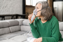 Upset Senior Woman Feeling Unwell, Has Shortness Of Breath, Asthma, Using Oxygen Mask Sitting On The Couch At Home. Sick Mature Woman Makes Inhalation With A Nebulizer At Home, Treating Herself