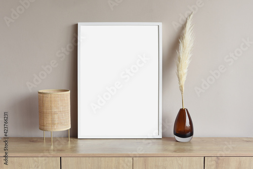 Fototapeta Blank picture frame mockup on gray wall. White living room design. View of modern scandinavian style interior with artwork mock up on wall. Home staging and minimalism concept obraz