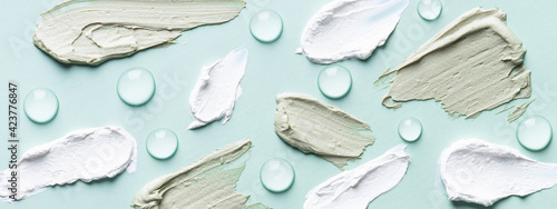 Green and white clay smears and hyaluronic acid serum drops on turquoise background.