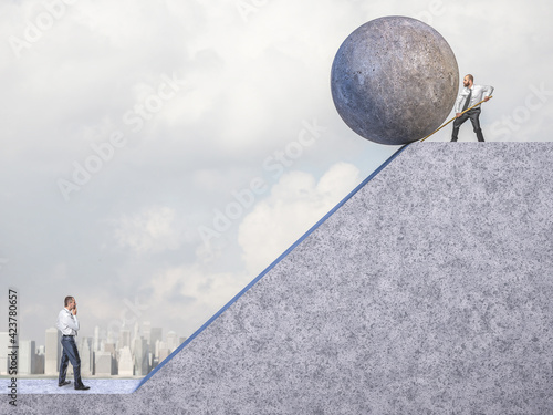 businessman pushes big concrete sphere towards the slope where there is another man Fototapeta