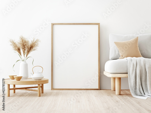 Fototapeta Vertical poster mockup with wooden frame standing on floor in living room interior with sofa, beige pillow, dried Pampas grass and Japandi decor on empty wall background. 3D rendering, illustration obraz