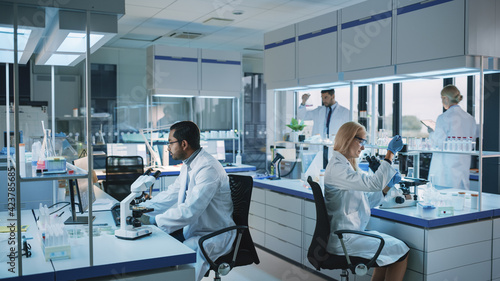 Team of Medical Research Scientists Conduct Experiments with Help of Microscope, Test Tubes, Micropipette and Writing Down Analysis Results on a Computer. Modern Biological Applied Science Laboratory.