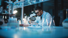 Medical Development Laboratory: Caucasian Female Scientist Looking Under Microscope, Analyzes Petri Dish Sample. Specialists Working On Medicine, Biotechnology Research In Advanced Pharma Lab