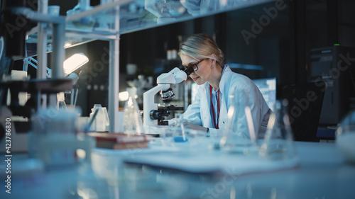 Photo Medical Development Laboratory: Caucasian Female Scientist Looking Under Microscope, Analyzes Petri Dish Sample