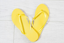 Yellow Flip-flops On A White Wooden Background Close Up