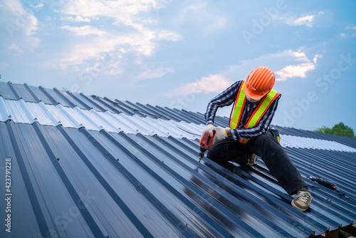 Tela Asian Roofer worker safety wear using air or pneumatic nail gun and installing on new roof metal sheet, Roof concept of residential building under construction
