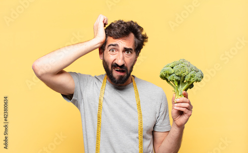 young crazy bearded man dieting angry expression and holding a cabbage Fotobehang