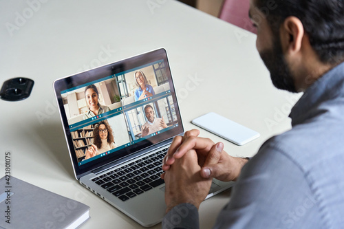 Indian business man having virtual team meeting on video conference call using laptop work from home office talking to diverse people group in remote teamwork online distance chat Fototapet