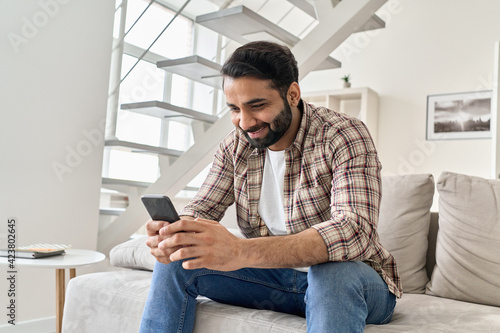 Foto Happy young indian man using smart phone sitting on couch at home