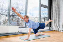 Middle Age Man Stay On Floor Mat In Plank Pose, Stretch Hands And Legs At Light Studio Background, Healthy Workout. Plank With Opposite Arm And Leg Lift.