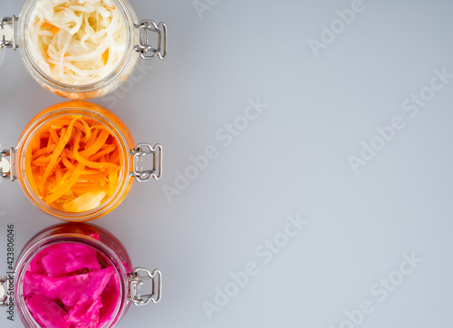 Canvas-taulu Homemade village fermented sauerkrauts, red cabbage and korean carrot in glass jars, gray background