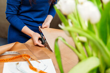 A Woman Fashion Designer Cuts Black Scissors Cutting Out On Kraft Paper Next To A Meter Of Patterns In The Foreground Flowers Tulips. Home Sewing Training Online
