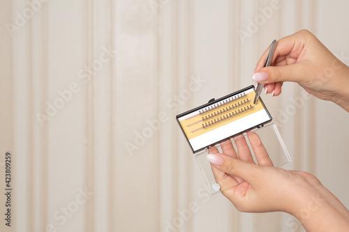 Fotografia, Obraz Woman hand holding lash bundles and tweezers
