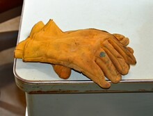 Old Dirty Yellow Work Gloves Lying On Desk