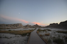 Landscape View Of The Unusual Rocky Terrain At Badlands National Park During Twilight, With The Moon In The Sky
