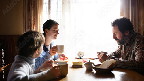 Obraz Portrait of poor sad small girl with parents eating indoors at home, poverty concept. - fototapety do salonu
