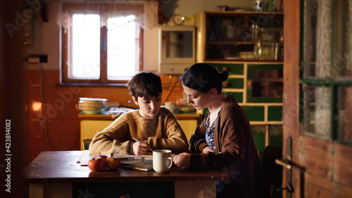 Obraz Poor mature mother and small daughter learning indoors at home, poverty concept. - fototapety do salonu