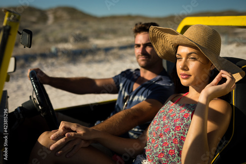 Happy caucasian couple sitting in beach buggy by the sea holding hands