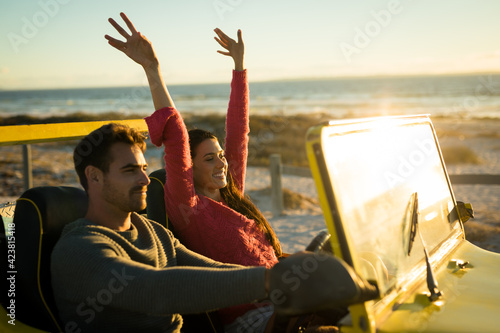Happy caucasian couple sitting in beach buggy by the sea during sunset
