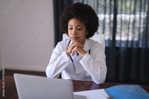 African american female doctor sitting making video call consultation