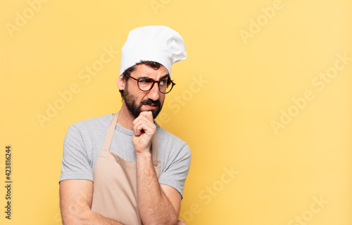 Cuadros en Lienzo young bearded chef man doubting or uncertain expression