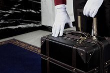 Doorman Is Holding A Suitcase. Unrecognizable Photo. Only White-gloved Hands. Hotel Service. Hotel Business.Meeting Guests At The Hotel.