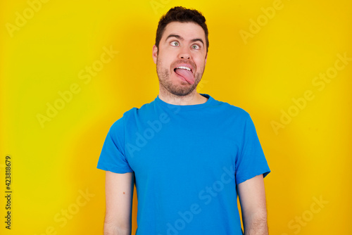 Fotografie, Obraz young handsome caucasian man wearing blue t-shirt against yellow background showing grimace face crossing eyes and showing tongue