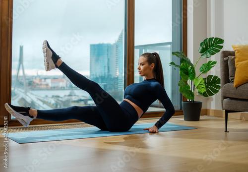 Fotografia Sportive brunette with brown ponytail does leg exercises
