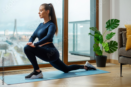 Obraz Brunette in tracksuit practices yoga on mat by lodge window - fototapety do salonu