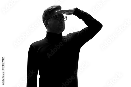 Fotografia, Obraz Silhouette of man peering ahead into the distance, with hand on his forehead