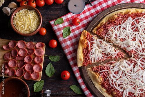 Pizza de calabresa com queijo mussarela, cebola e molho de tomate