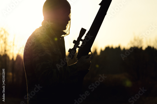 Valokuva silhouette of an arrow with a rifle and a sight, on the hunt