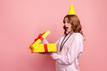 Profile Of Amazed Happy Teenage Girl In Hoodie Opening Gift Box With Opened Mouth, Satisfied With Present. Indoor Studio Shot Isolated On Pink Background