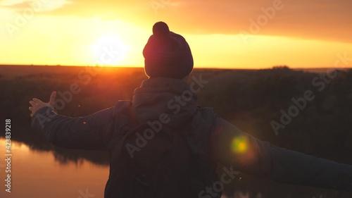 Fotografia Man traveler whirls at sunset and laughs, adventurer in free flight of fantasy,