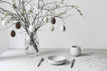 Easter Festive Table Setting. Fresh Branches In Vase Decorated By Paper Ornaments. Hanging Chicken Eggs With Quail Festher.Spring Interior Decoration. Scandinavian Minimal Design. Cup Of Coffee.