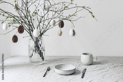 Fototapeta Easter festive table setting. Fresh branches in vase decorated by paper ornaments. Hanging chicken eggs with quail festher.Spring interior decoration. Scandinavian minimal design. Cup of coffee. obraz