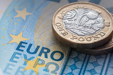 """British One Pound Coin Placed On Top Of 20 EURO Banknote With Visible Words """"EURO"""" Translated In Different Languages. Concept. Selective Focus. Macro."""