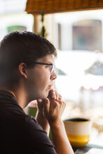 Young Man At A Cafe Looking Out The Window