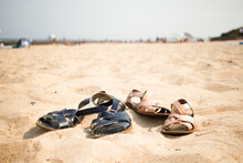 Two Pairs Of Children's Sandals Lying On The Beach