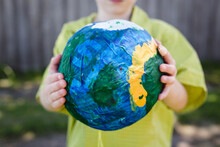 Boy Holding Up A Paper Mâché Ball